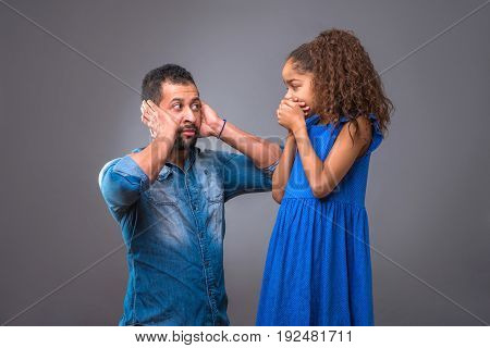 A young black man covering his ears while his daughter covering her mouth with her hands