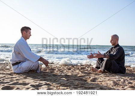 Karate fighters meditate after training on the beach