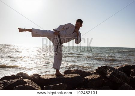 picture of male karate fighter posing on stones sea background