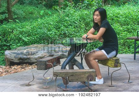 Relaxation Concept : Woman sitting relax on wooden chair at outdoor garden surrounded green natural.