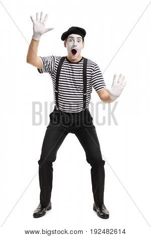 Full length portrait of a mime holding his hands on an invisible wall isolated on white background