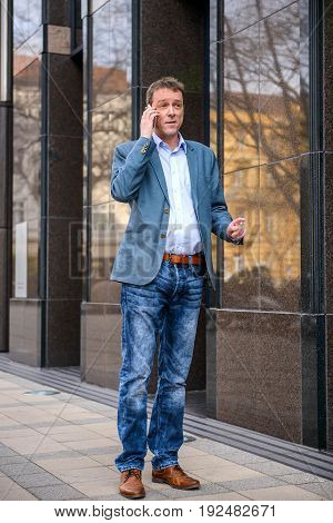 A middle age businessman walking next to the office building while talking on his phone