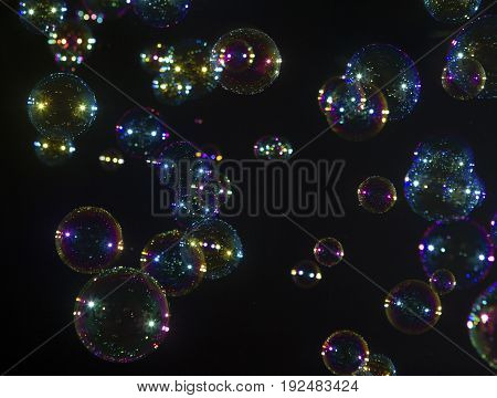 colourful bubble soaps over a black background