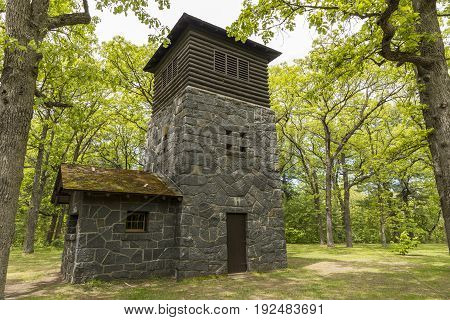 A water tower of unique architecture in the woods.