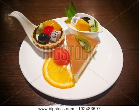 Close-up cheese cake fruit tart and cheese mousse with sliced orange kiwi grape mango and dragon fruit on white plate over wooden table