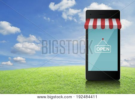 Modern smart mobile phone with online shopping store graphic and open sign on green grass field over blue sky Shop online concept