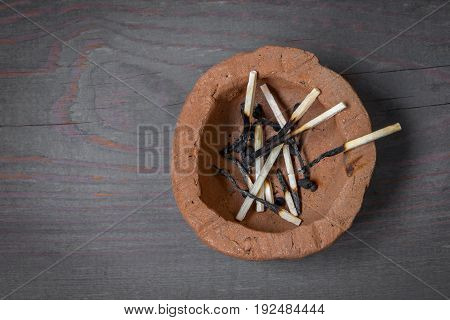Burnt wooden matches lie in a clay ashtray