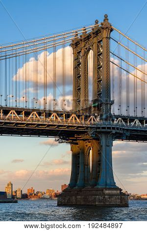 Detail of the Manhattan Bridge east tower over the East River at sunset. New York City
