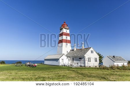 Colorful lighthouse in the small fishing community of Alnes on Godoy island on the west coast of Norway