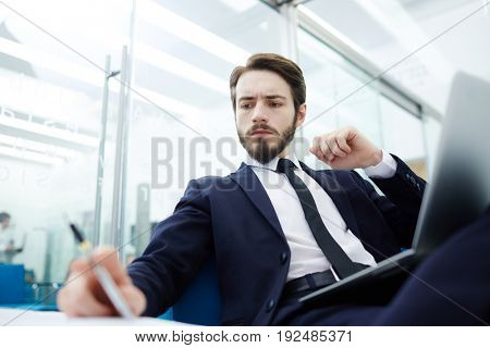 Busy salesman reading financial papers