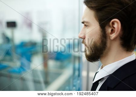Serious employee looking through office window