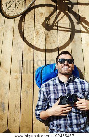 Relaxed man with photocamera enjoying vacation