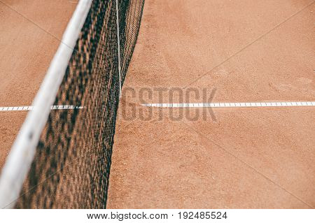 Tennis court with a grid for professional games. White lines on a brown field for a game.