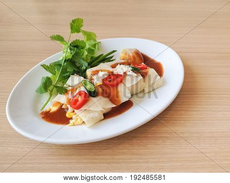 Fresh spring rolls stuffed with egg and vegetable topped with sliced chilli pepper served with brown sauce green onion and cilantro on white plate over wooden table background with copy space