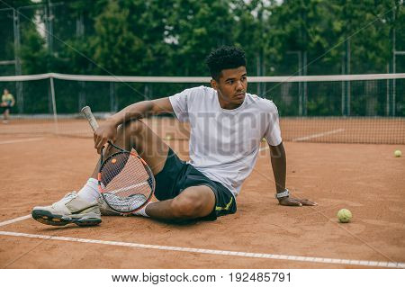 Exhausted male tennis player sitting on ground after tennis game, refreshing, cooling himself. Serious african man relaxing after good game.
