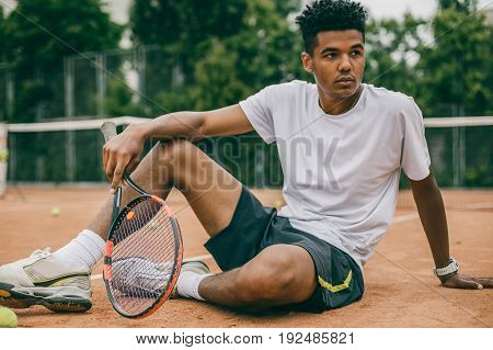 African man and short break during the tennis game. Young man in sports uniform sits on the ground of a tennis court.