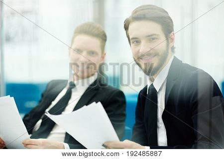 Two traders or bankers with papers looking at camera