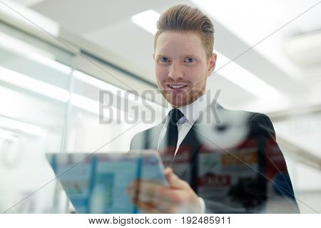 Successful businessman with touchpad looking at camera