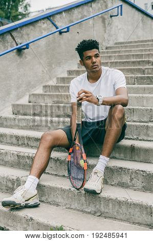 Handsome black guy in polo sits on concrete steps. Tennis player holds racket and ball.