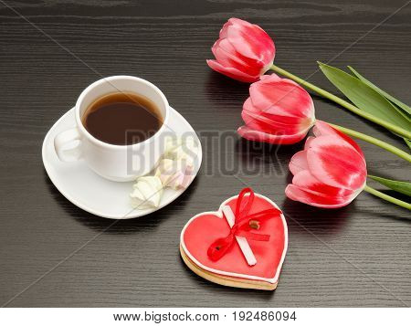 Mug Of Coffee, Marshmallows And Heartshaped Gingerbread, Three Pink Tulips. Black Background.