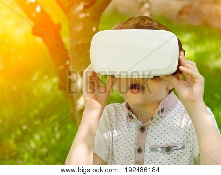 Boy in a virtual reality helmet on a background of green forest. Toning