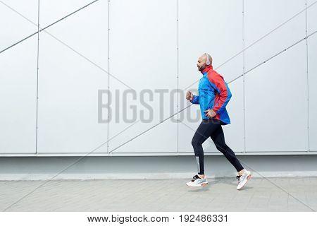 Marathone runner with headphones training outdoors