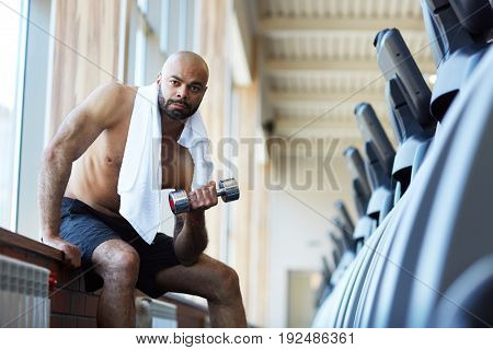 Bald young man with dumbbells working out in gym