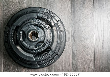 Weights. Barbell plate on the gym floor.