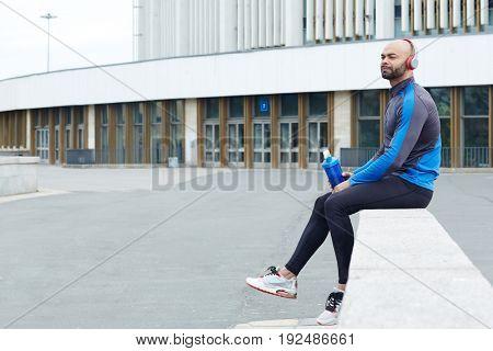 Handsome guy in activewear having refreshment