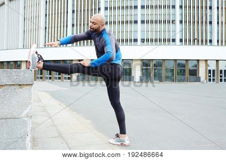 Young athlete exercising on background of urban edifice
