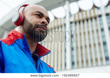 Active guy with headphones running at leisure