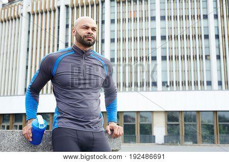 Calm athlete with plastic bottle having short rest before new training