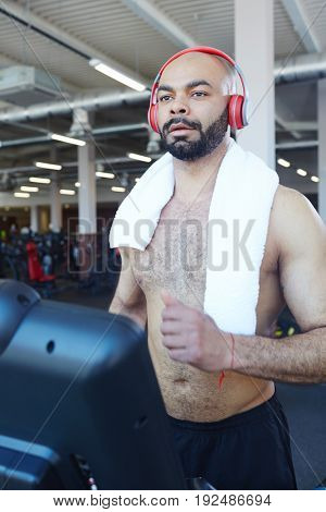 Young man listening to music while running on treadmill