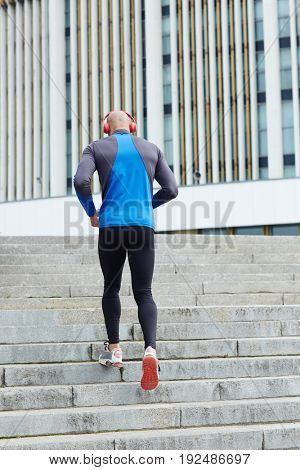Young man jogging upwards the staircase