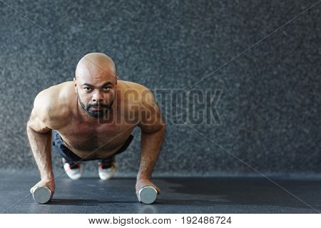 Fit and muscular man doing planks on the floor