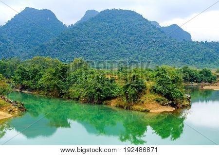 A River With Green Water And Clay Banks