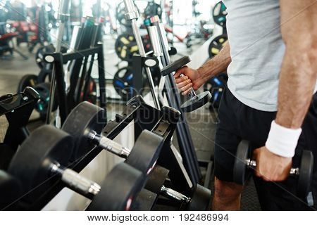 Sportsman choosing barbells for exercising