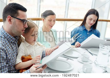 Family of four reading menu in restaurant