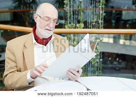 Grey-haired senior man reading menu in restaurant