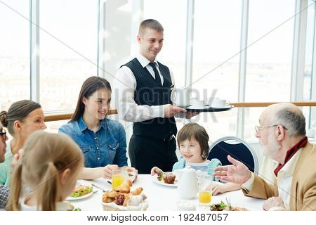 Family of six having meals in restaurant with waiter near by