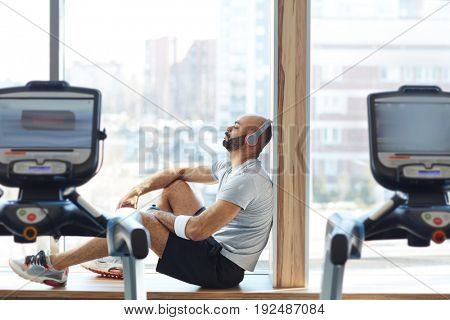 Relaxed man sitting on window-sill after training in gym