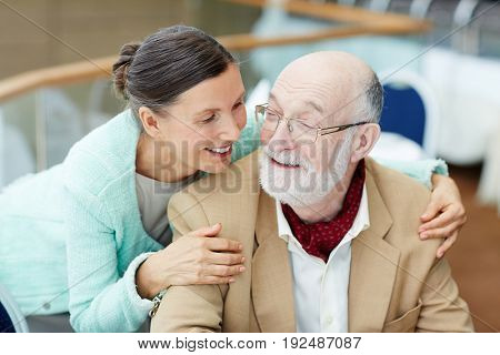 Affectionate senior woman talking to her husband while embracing him