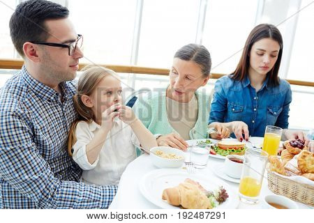 Young couple, their daughter and mature woman sitting by dinner table