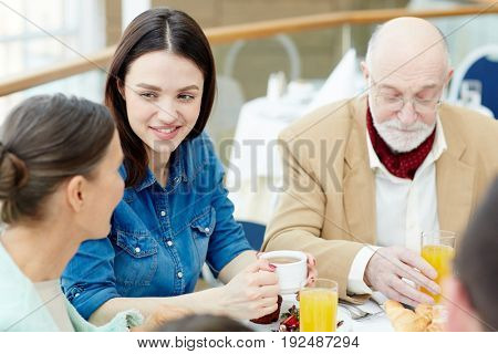 Young woman talking to her mother by breakfast