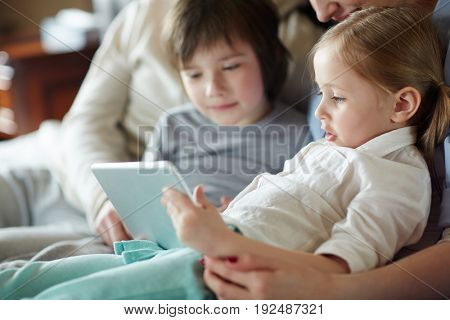 Adorable siblings watching online cartoons with parnts n ear by