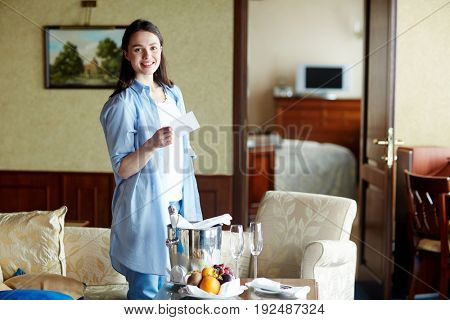Young female standing in dining-room in hotel