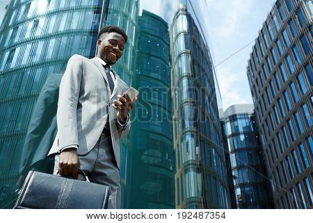 Broker with smartphone standing by modern building