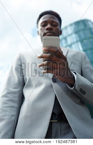 Man in suit texting outdoors