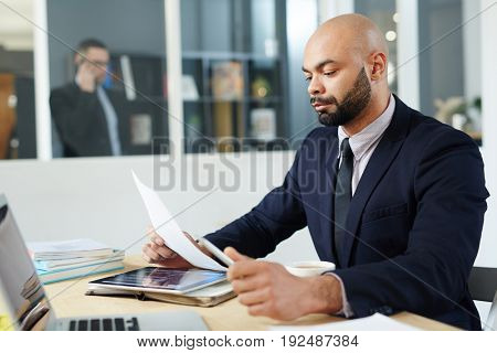 Serious economist concentrating on reading document