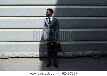 Elagant manager with briefcase against wall of urban building